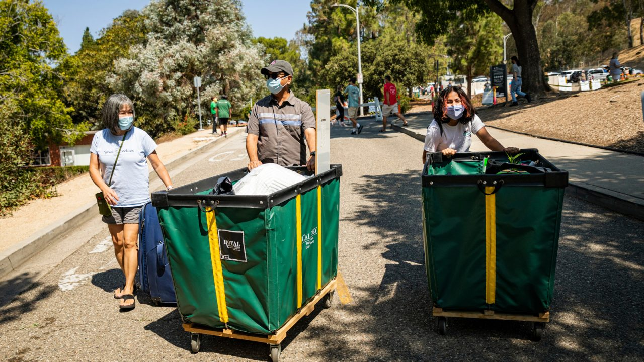 A student and her parents, smiles evident under face coverings, push green and yellow carts loaded with dorm supplies up a campus driveway.