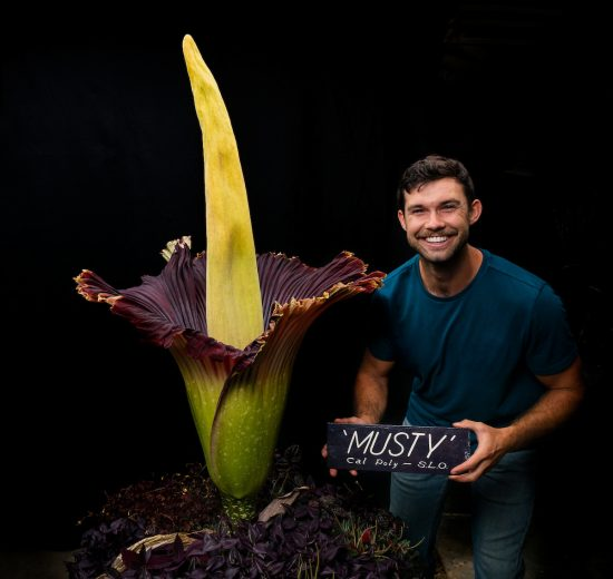 "A young man holding a sign reading ""Musty"" smiles next to a massive tropical corpse flower"