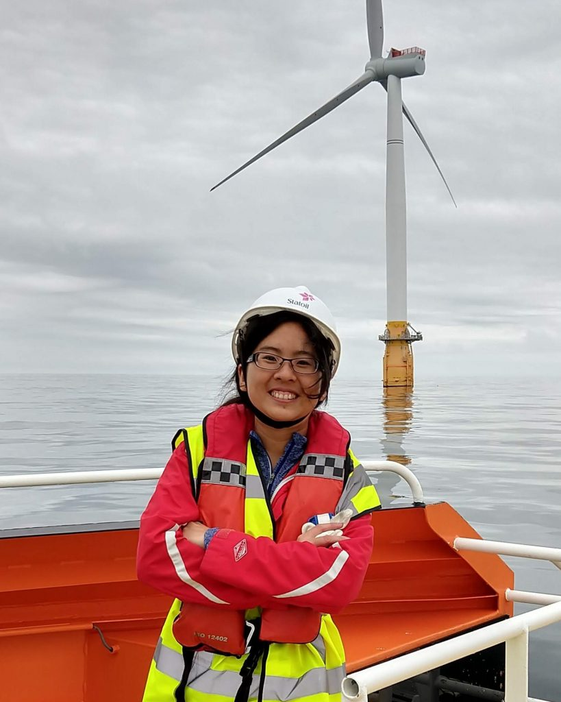 A young woman in a life vest and hardhat smiles on the deck of a boat in front of an ocean-mounted windmill.