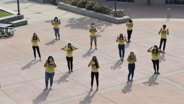 Taken from above, a group of students in bright yellow shirts stands spaced apart in the University Union plaza.