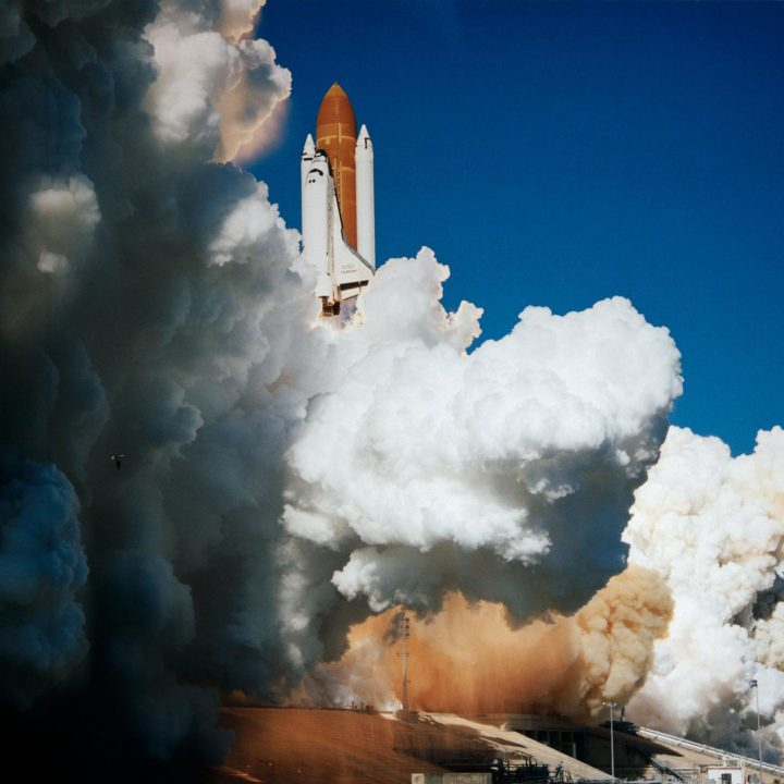 The Space Shuttle Challenger lifts off from Earth surrounded by steam