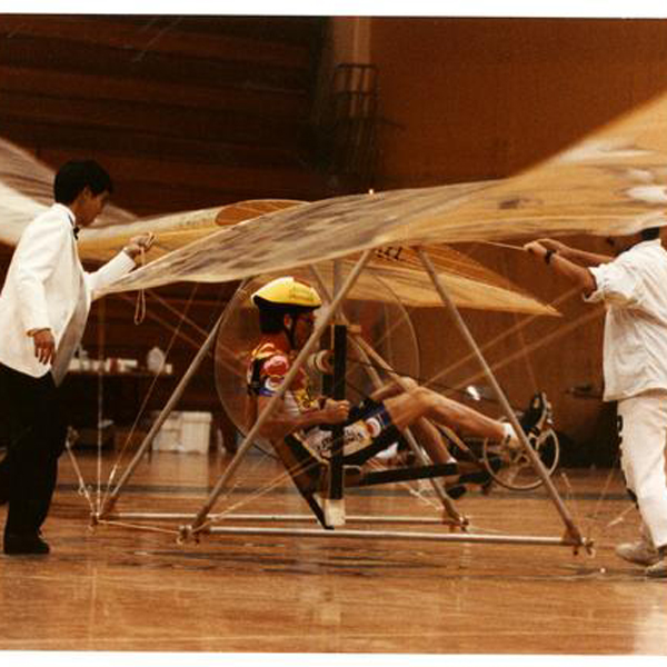 Three students test a human powered helicopter in Mott Gym at Cal Poly