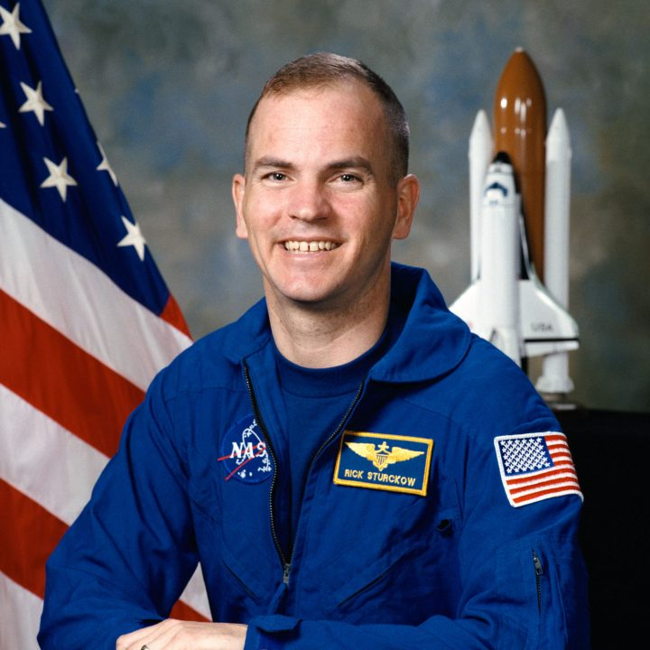 "Astronaut Frederick ""CJ"" Sturckow smiles in his blue flight suit in front of an American flag and a model of the Space Shuttle"