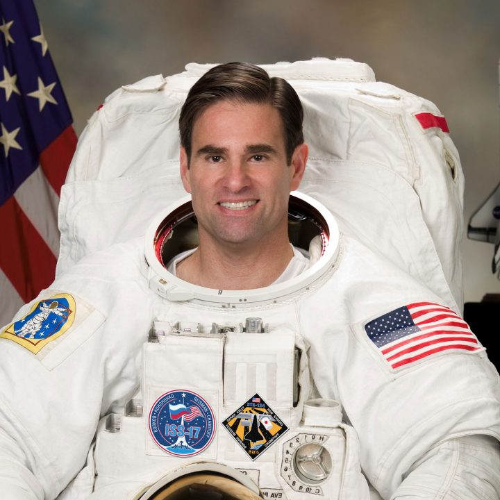 Astronaut Greg Chamitoff smiles in his space suit