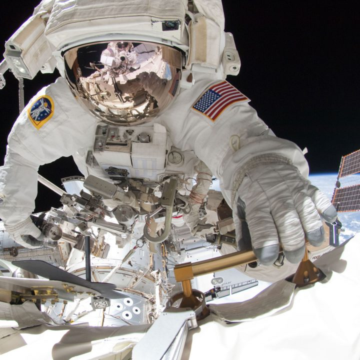 An astronaut holds onto the side of the International Space Station during a spacewalk