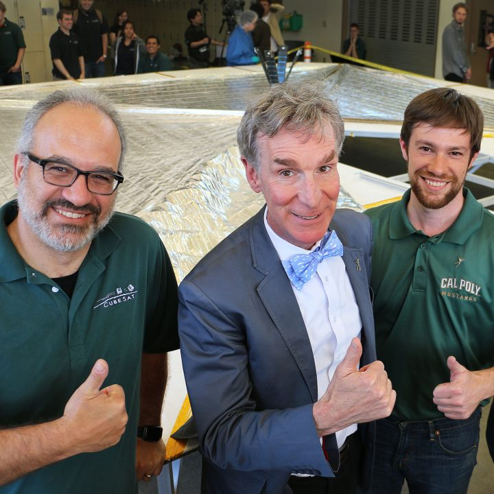 Bill Nye stands with two Cal Poly faculty in front of an unfurled mylar solar sail