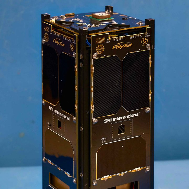 A cubesat with the words 'PolySat' engraved on it stands in front of a blue background