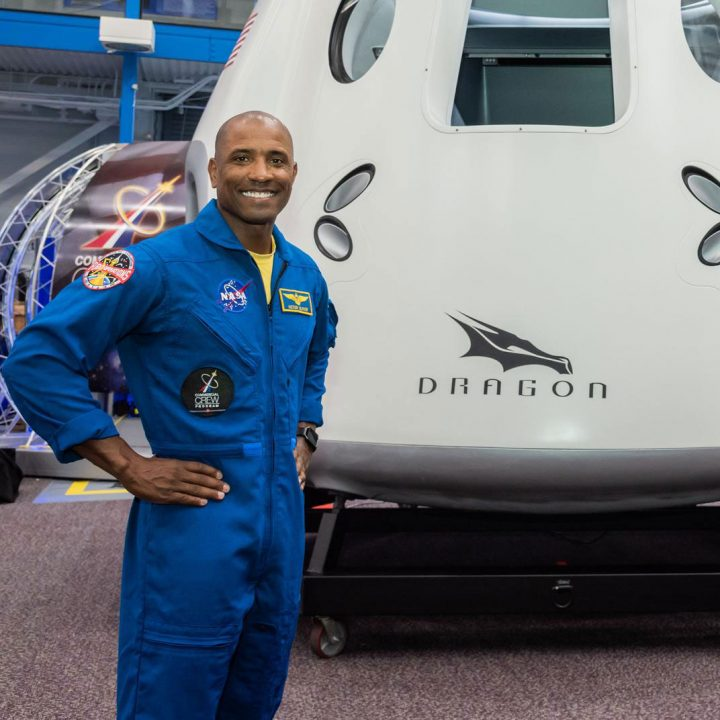 Astronaut Victor Glover stands in front of a SpaceX Crew Dragon capsule wearing a blue flight suit
