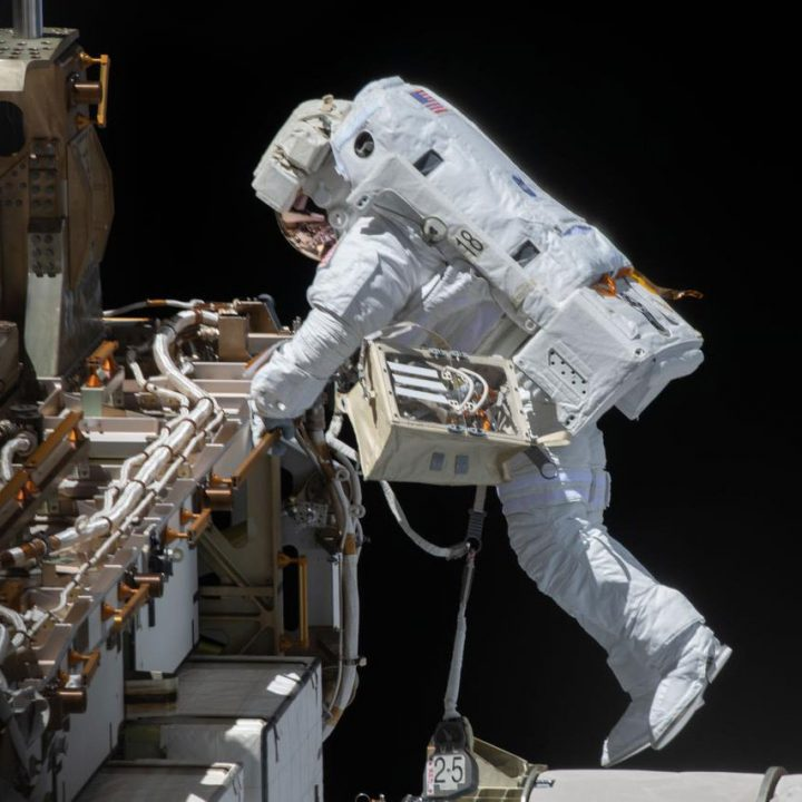 An astronaut in a white spacesuit performs a spacewalk outside the International Space Station