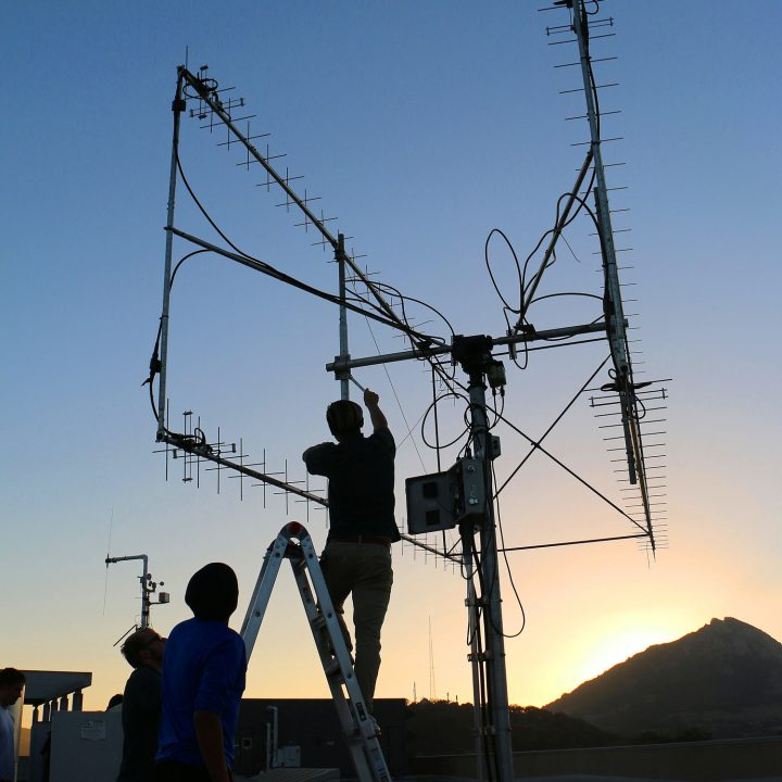 Two people fix an antenna on the roof of a building with the sun setting behind Bishop Peak in the background