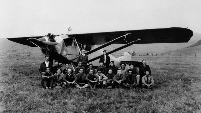 A black and white image of students and faculty sitting in front of an airplane in 1927