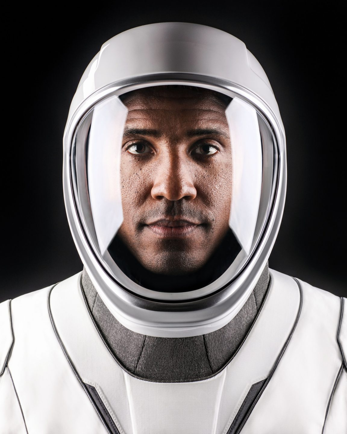 A man gazes into the camera in a sleek, futuristic-looking helmet and suit.