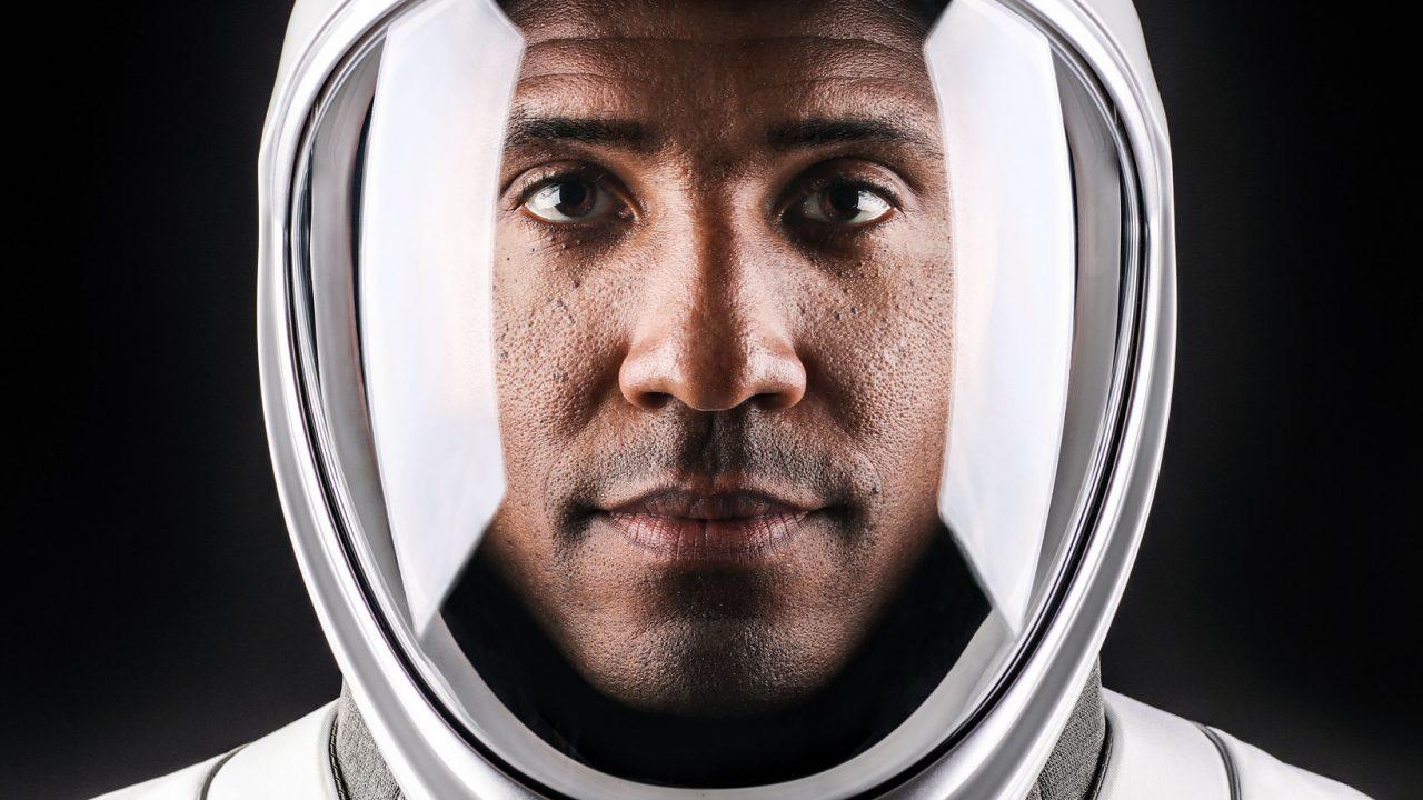 A man gazes into the camera through the glass of a sleek, futuristic space helmet