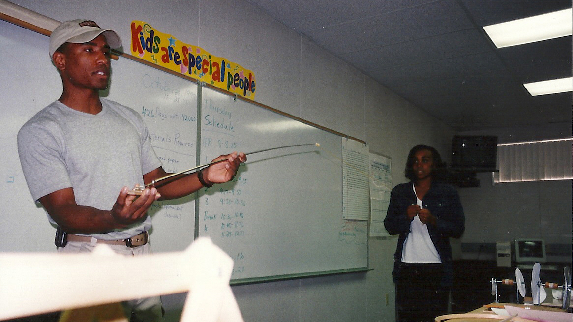 A younger Glover in a hat and t-shirt gestures in front of a middle school classroom whiteboard, while a young woman stands to the side watching.