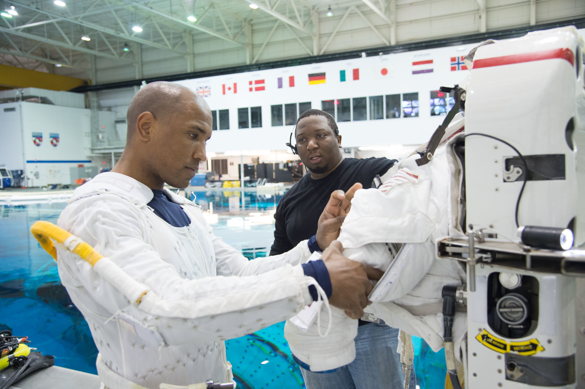 Glover in a white suit connected to a measuring device by tubes works with a technician in front of a large indoor pool.