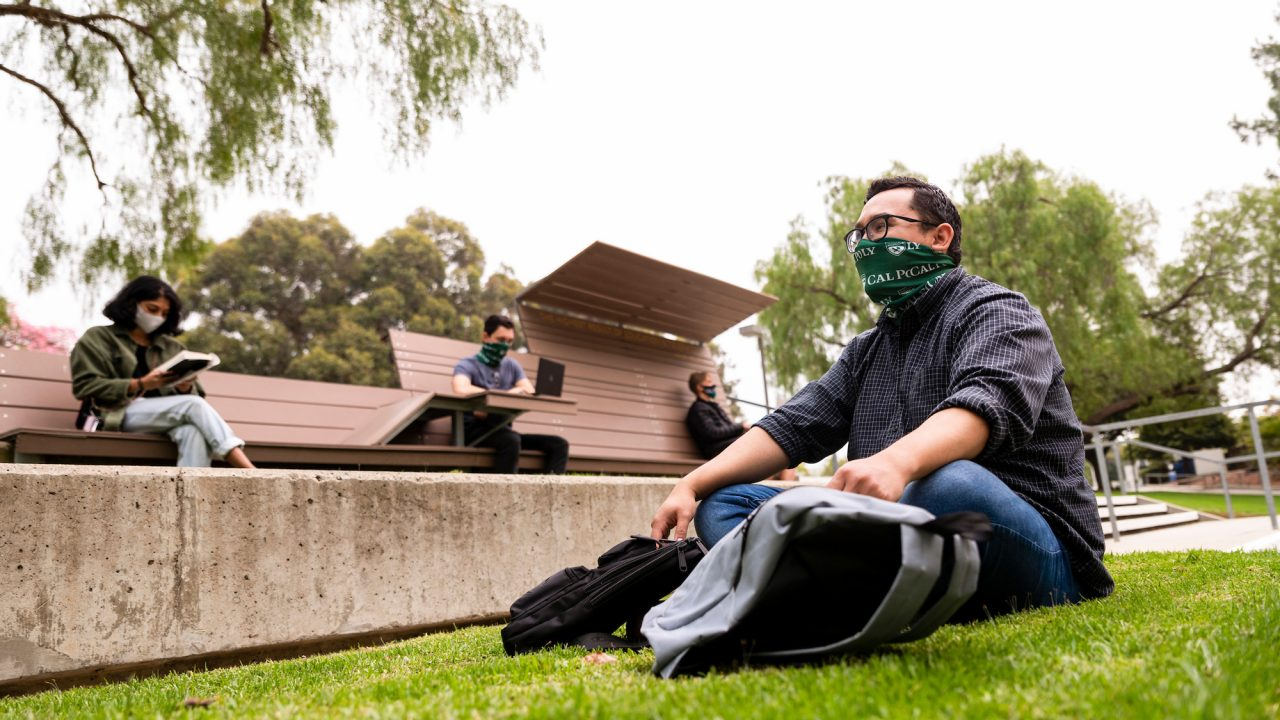 Four students sit on grass and benches wearing masks