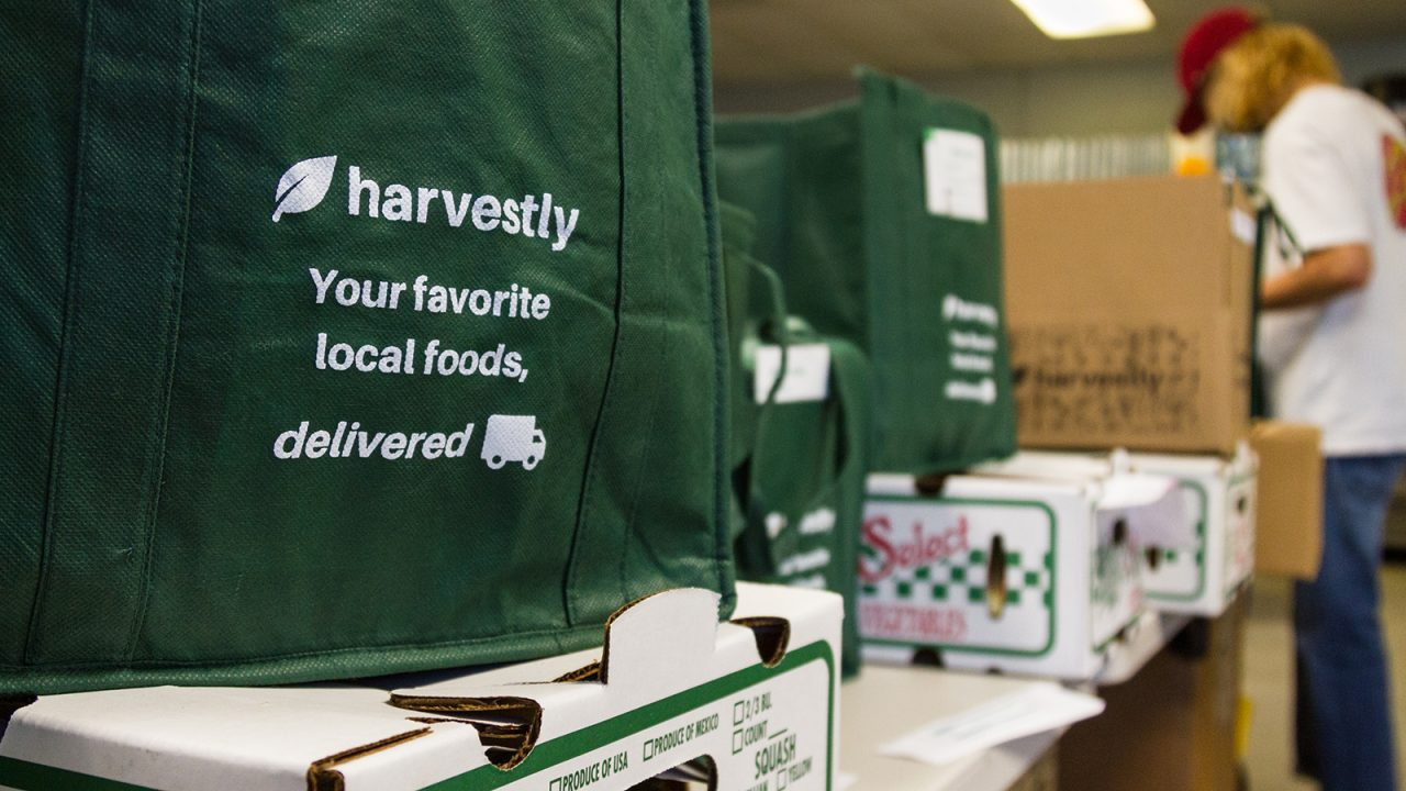 "A green tote back, filled with foods and printed with the words ""Harvestly - your favorite local foods delivered"" sits on a table with produce boxes, while a young man in the background packs another bag."