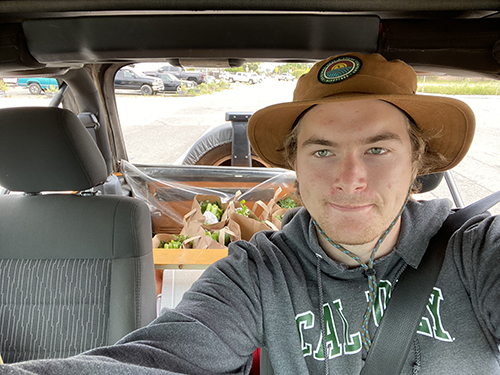 A selfie of a young man in a wide brimmed had and a Cal Poly sweatshirt in the front seat of a car filled with boxes of food.