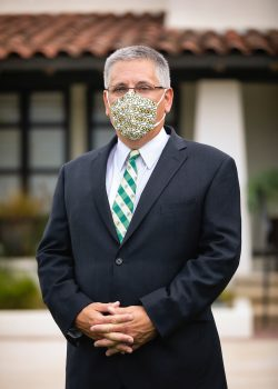 President Armstrong stands in front of the Cal Poly presidential residence wearing a dark suit and a facemask covered in CP marks