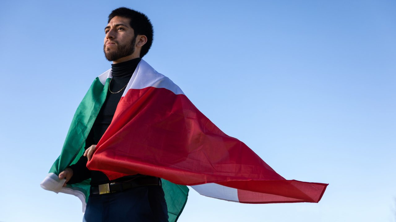 A man stands with the Mexican flag draped over his shoulders