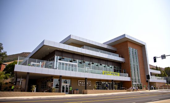 A terraced three-story building of glass, steel and brick