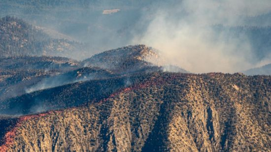 A hilside smoldering in the wake of a wildfire