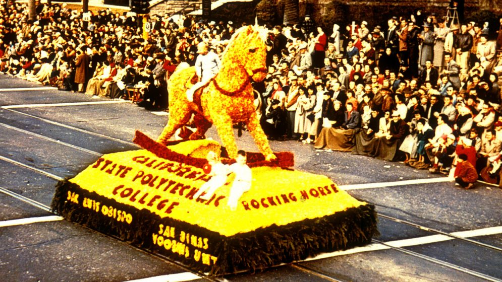 A flower-covered float depicting a rocking horse with a child sitting on top