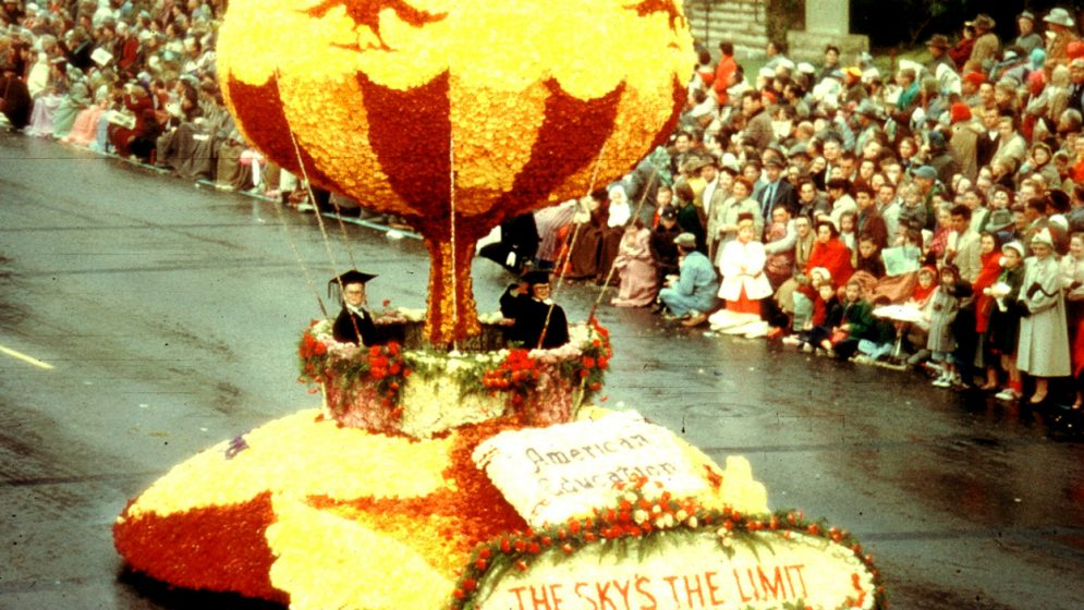 Two children in caps and gowns sit on a rose covered float depicting a hot air baloon