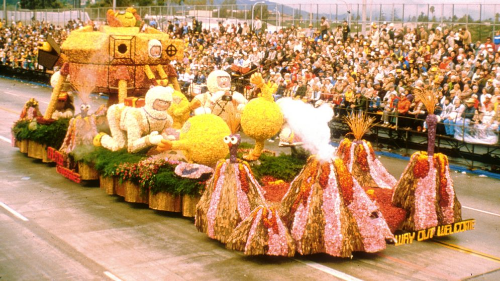 A rose-covered parade float of astronauts taking photos of aliens