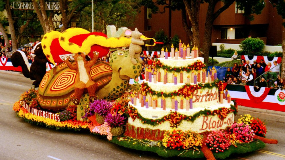 A rose-covered parade float depicting animals blowing out birthday candles on a cake