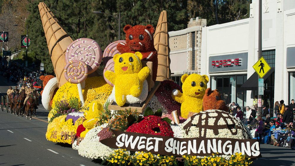 A rose-covered parade float depicting gummy bears and ice cream