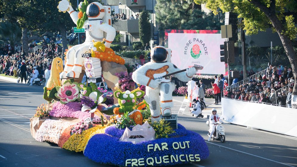 A rose-covered parade float depicting astronauts playing muiscal instruments