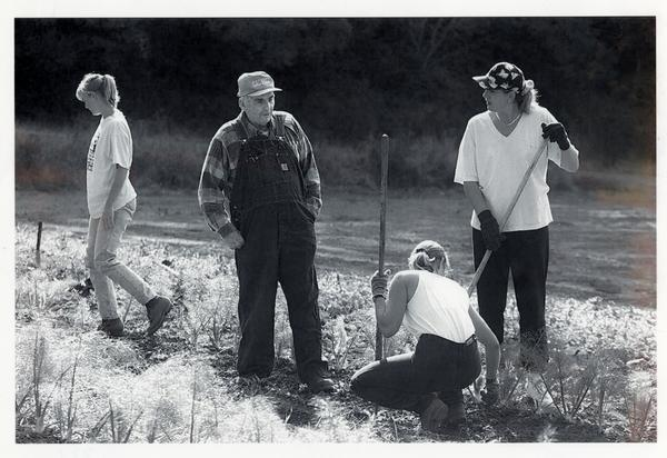 In a black and white photo, a man in overalls and a cap watches students working in a field.