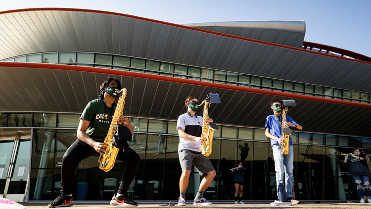 Three Cal Poly band members play saxaphone in front of the performing art center