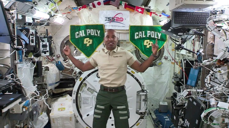 Astronaut Victor Glover floats in the International Space Station between two Cal Poly banners
