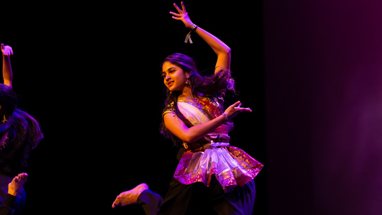 A student dances under the lights at Poly Cultural Weekend