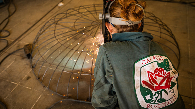 A student in a Cal Poly Rose Float jumpsuit welds metal