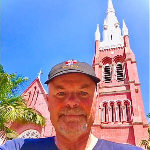 Jim McMorran stands in front of a tall brick structure