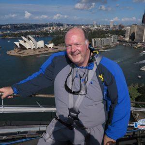 Jeff Land scales the Sydney Harbor Bridge overlooking Sydney Opera House