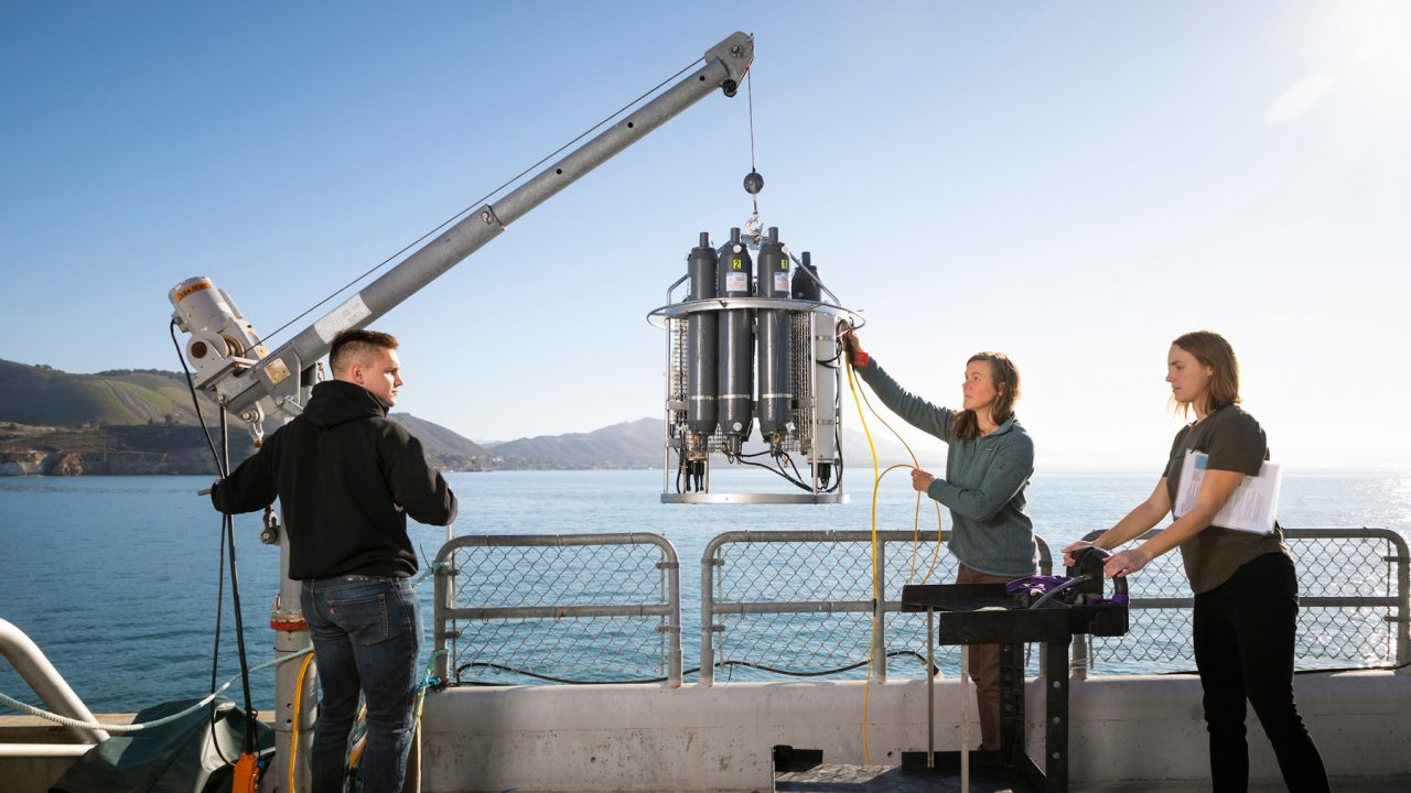 Three people lift machinery with a crane on the Cal Poly Pier