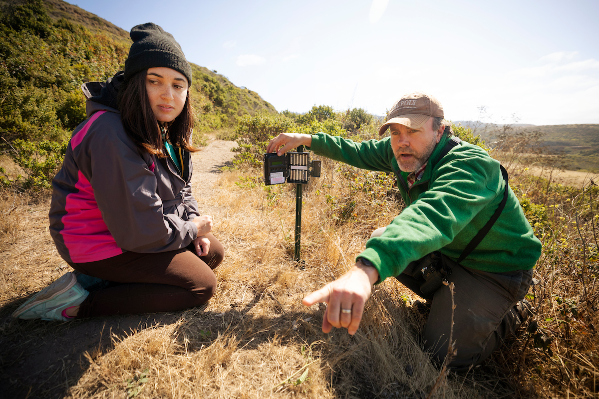 A young woman in a jacket and knit cap and an older bearded man in a baseball cap crouch in a field next to an animal sensor mounted on a stake