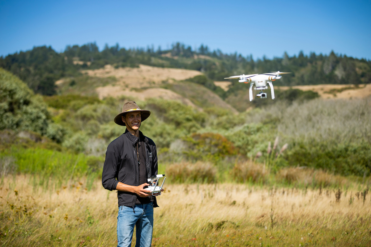 A young man in a wide brimmed hat pilots a camera drone over a grassy field on a hillside with forested mountains in the background