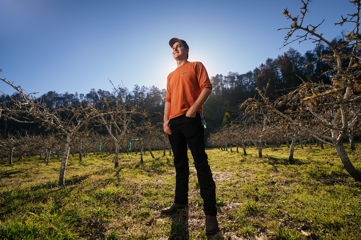 A young man in an orange shirt and baseball cap stands in an orchard with the sun behind him.