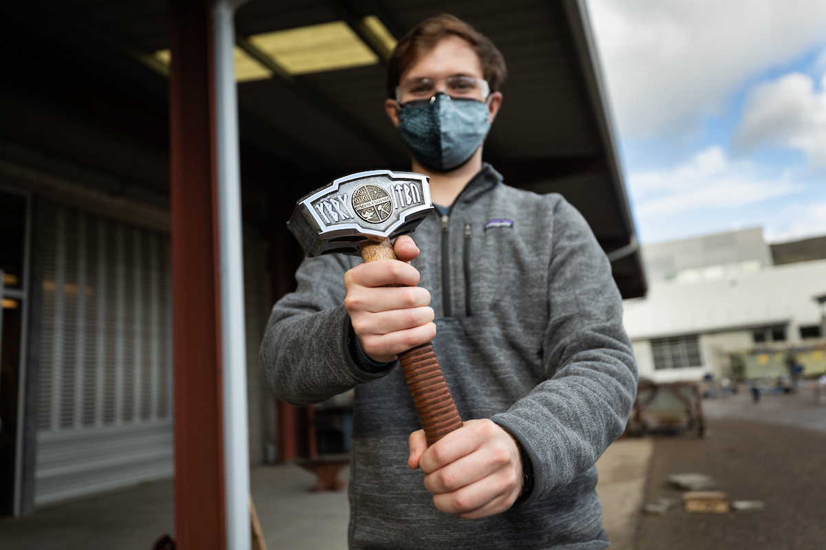 A student wearing a mask holds a custom-designed hammer