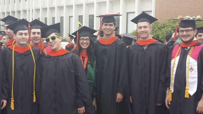 A group of 8 graduates in black robes and orange stolls smile