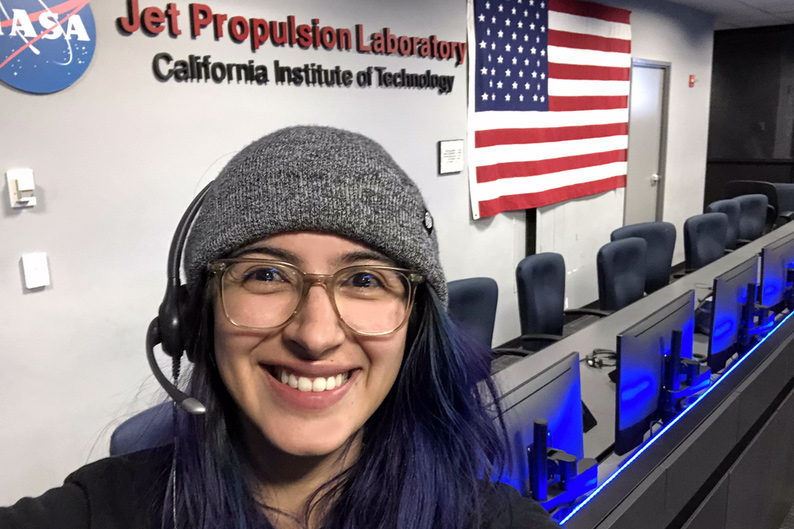 A person wearing glasses, a hat and a head set stands in the NASA Jet Propulsion Laboratory's Mission Control Room
