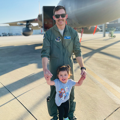 Jamie Hastings stands with his child in front of a fighter jet