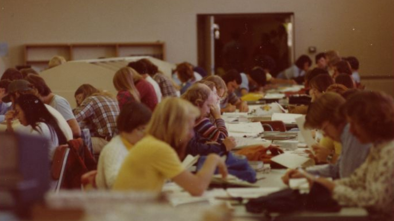 Students crowd around tables studying in a grainy photo from 1976