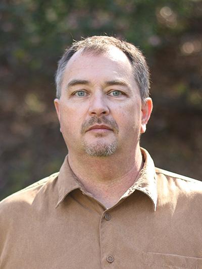 A portrait of professor Chris Den Hartog, standing outdoors wearing a tan shirt