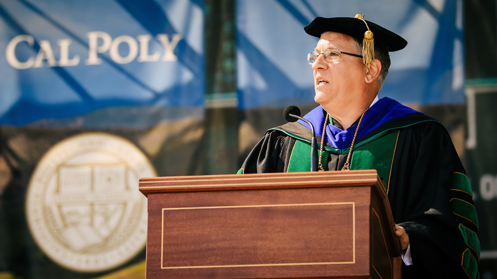 President Armstrong, in graduation regalia, stands at a podium with the sun shining on a Cal Poly banner behind him.